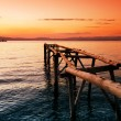 Primitive wooden pier at sunset - Stock Photo