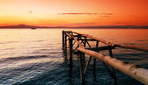 Primitive wooden pier at sunset — Stock Photo