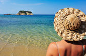Young woman in hat looking at small island — Stock Photo