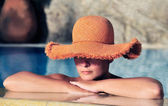 Attractive young woman in hat resting by the side of a pool — Stock Photo