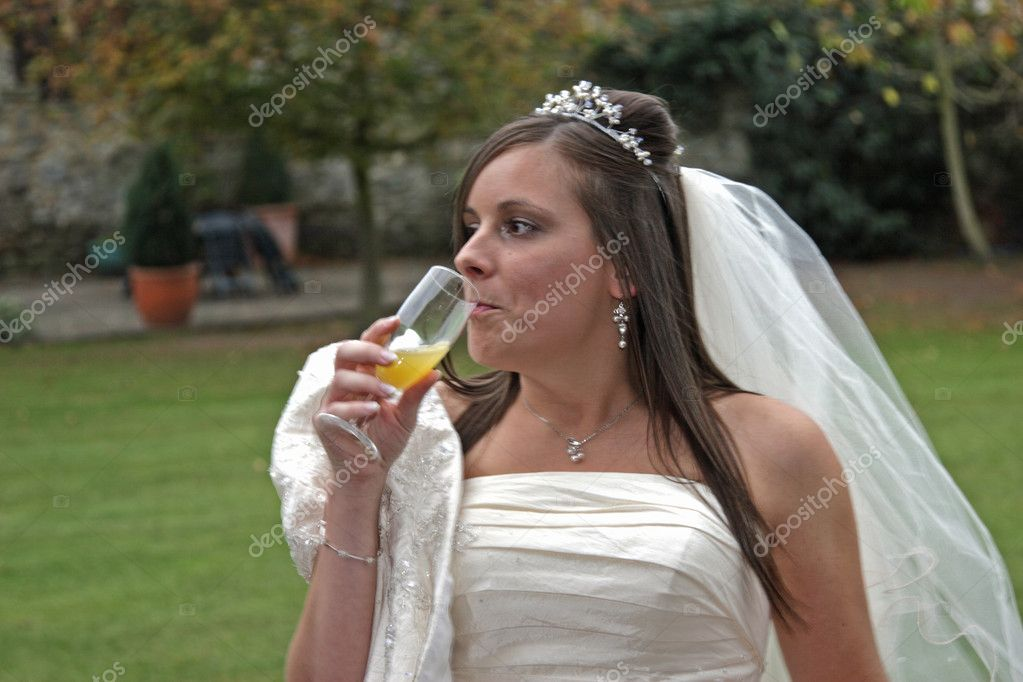 A young bride sipping a glass of Bucks Fizz — Stock Photo #3467801
