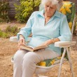 Stock Photo: Mature Lady Reading In The Garden