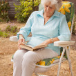 Mature Lady Reading In The Garden — Stock Photo #3562099