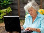 Dame âgée à l'aide d'ordinateur portable — Photo