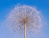 Fountain as dandelion on a blue sky background — Photo