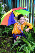 A girl with an umbrella sitting near the fence — Stock Photo