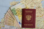 Passport and bank notes of euro on the map — Stok fotoğraf