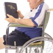 Old man in wheelchair reading a bible — Stock Photo