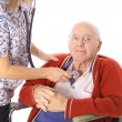 Royalty-Free Stock Photo: Nurse checking elderly mans pulse isolated on white