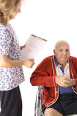Nurse checking elderly patient isolated on white — Stock Photo
