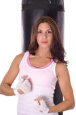 Fitness girl flexing in front of punching bag — Stock Photo