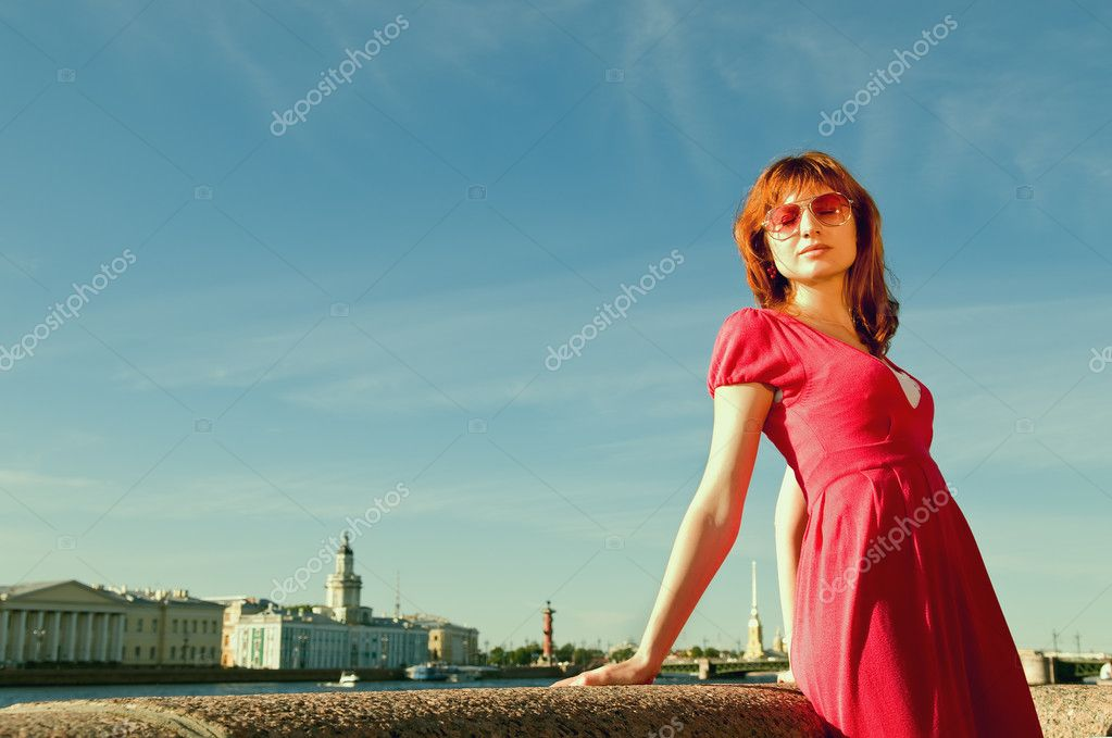 The young girl dreams on quay of the river with a kind on the bridge — Stock Photo #3653874