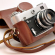 Used old-fashioned film photo-camera in leather case — Stock Photo #3577589