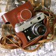 Vintage old film photocamera in leather case lying on very old photos — Stock Photo