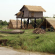 Hut and boat on the river bank — Stock Photo
