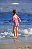 Little preschool girl jumping in waves — Stock Photo