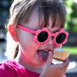 Little girl in sunglasses eating ice cream — Stock Photo