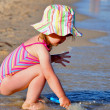 Stockfoto: Little toddler girl portrait playing on beach with shovel