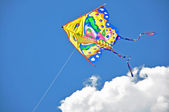 Colorful kite soaring in a blue sky — Stock Photo