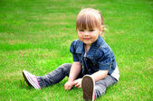 Little girl sits on the grass — Stock Photo