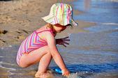用铁铲在海滩上玩的小蹒跚学步的女孩肖像 — 图库照片