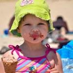 Little girl in sunglasses eating ice cream — Stock Photo #3628646