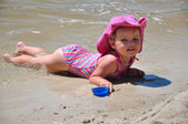 Pretty little girl lying on sandy beach — Stock Photo