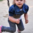 Pretty toddler girl riding on swing — Stock Photo