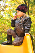 Little girl weared like a rock star sitting on slide — Stock Photo
