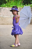 Toddler girl with umbrella at the street — Stock Photo