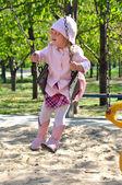 Pretty toddler girl riding on swing — Foto de Stock