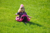 Happy little girl sitting on the green lawn — Stock Photo