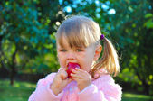 Cute little girl eating an apple outdoors — Stock Photo