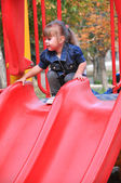 Cute preschool girl is going to ride on slide — Stock Photo