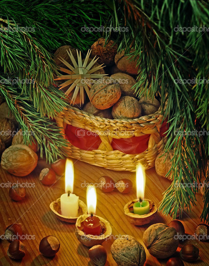Christmas still life with a nuts in basket and candles — Stock Photo #3764649