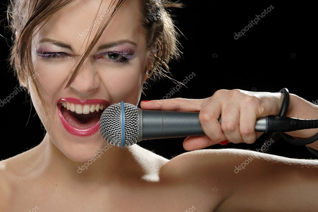 Portrait of a young singer with a microphone on a black background — Photo #3548519