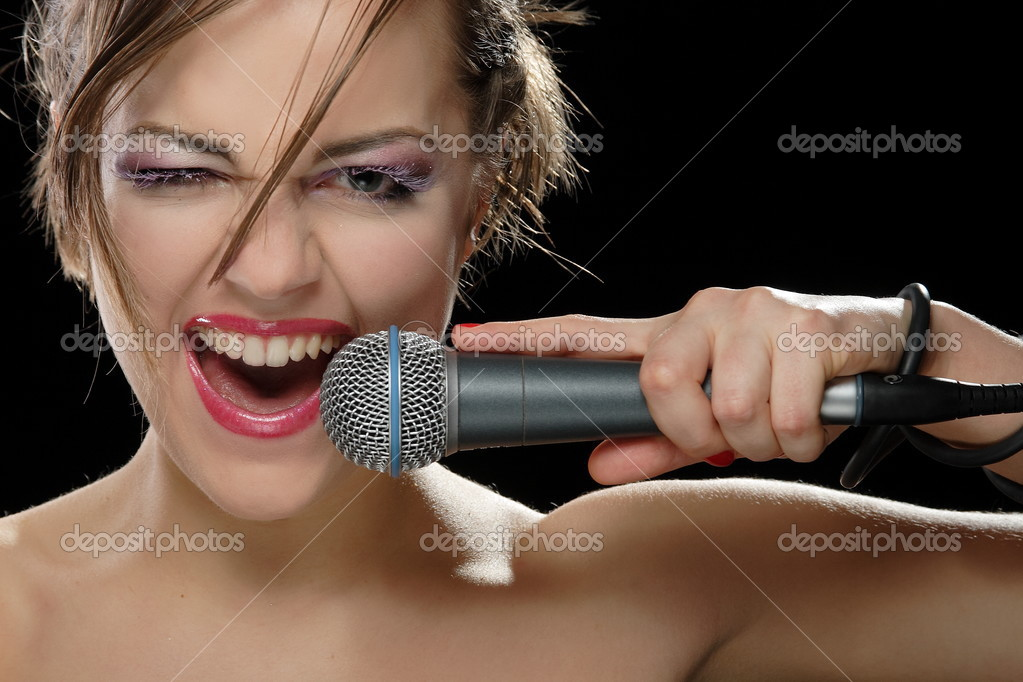 Portrait of a young singer with a microphone on a black background  Stockfoto #3548519