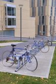 Bicycles parked and locked in bike rack in front of buildings. — Stock Photo