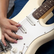 Young woman playing white electric guitar — Stock Photo