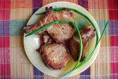 Carne frita con cebollas en un plato sobre una alfombra de rayas. — Foto de Stock