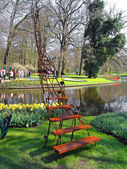 A sculpture in a botanical garden on the bank of lake, a ladder in the sky — Stock Photo