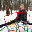 The girl sits on a twine on a children's design in park in the winter — Stock Photo #4917888