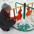 The girl sits about a children's roundabout in park in the winter — Stock Photo