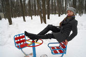 The girl sits on a children's roundabout in park in the winter — Stock Photo