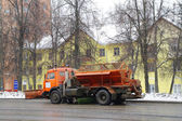 The lorry cleans road from a dirt and snow against the yellow house — Stock Photo