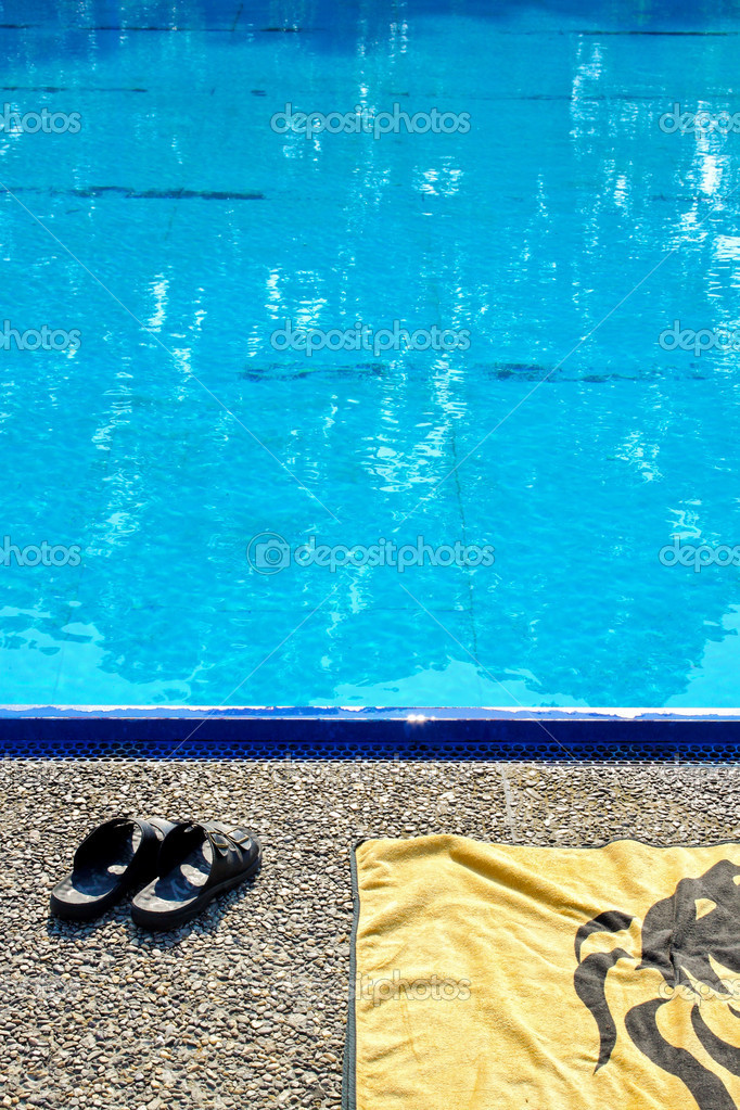 Towel and slippers standing near the edge of swimming pool  Stock Photo #3628532
