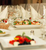 Table in restaurant with fine food and wine glasses — Stock Photo
