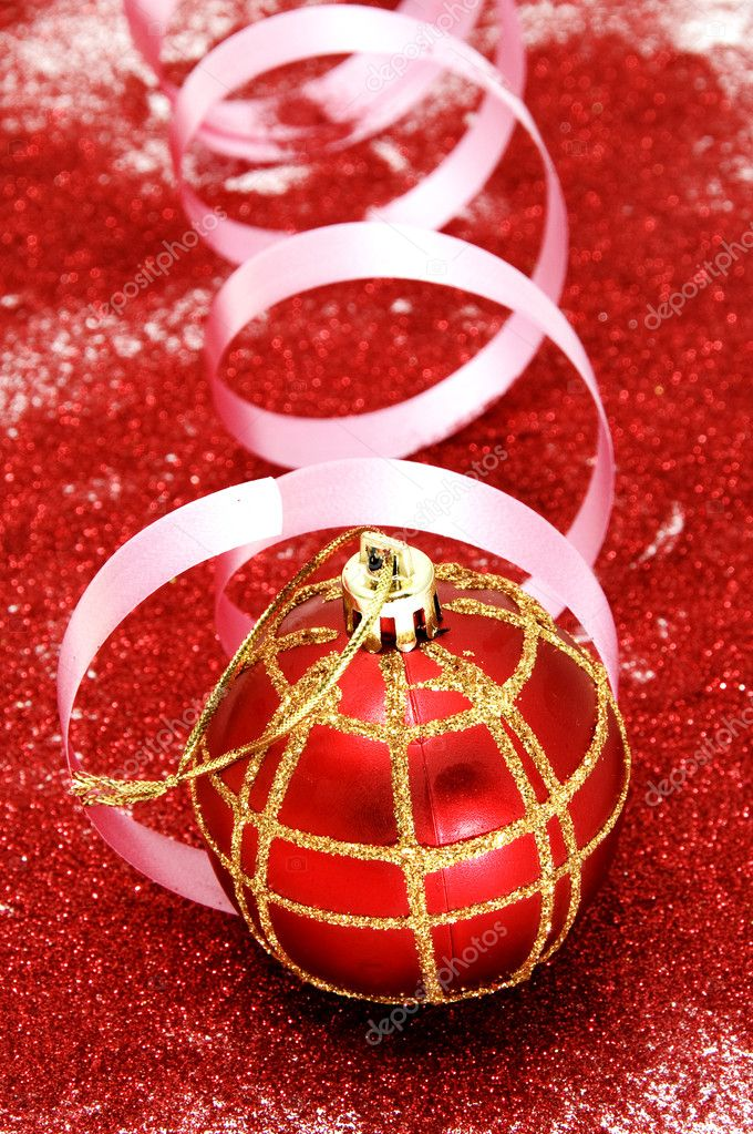 Red and golden christmas ball with a pink ribbon in a red glitter background  — Stock Photo #3744625