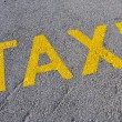 A taxi stand sign painted on the street - Stock Photo