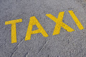 A taxi stand sign painted on the street — Stock Photo